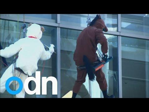 Window cleaners in costumes entertain locals in Tokyo