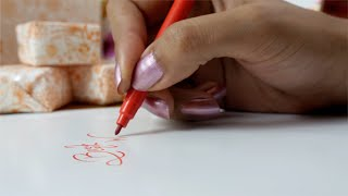 Close shot of a female writing best wishes on a birthday card