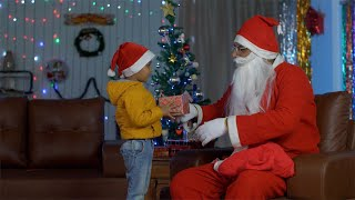 Old Santa Claus giving Christmas present to a smiling little boy on Christmas in India