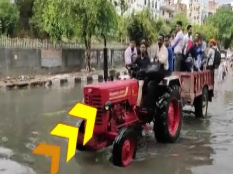 Delhi - Tractor owner charging Rs 10 to help cross water logged underpass