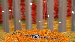 Designer rakhi placed on a rotating plate with flowers for Raksha Bandhan