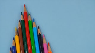 Pan shot of different colored school pencils beautifully arranged on a blue platform