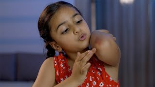 Portrait of a cute Indian innocent girl kid blowing air on elbow wound