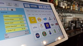 Shows a bar / restaurant managing orders by switching between the pos kds (kitchen display system). point of sale systems typically are one or other bu...
