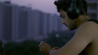 Young Indian man / male listening to music while standing in his house balcony