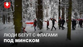 Люди в масках бегут с бело-красно-белыми флагами под Минском 17 января
