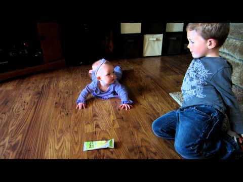 Big brother helping baby sister learn to crawl.MOV