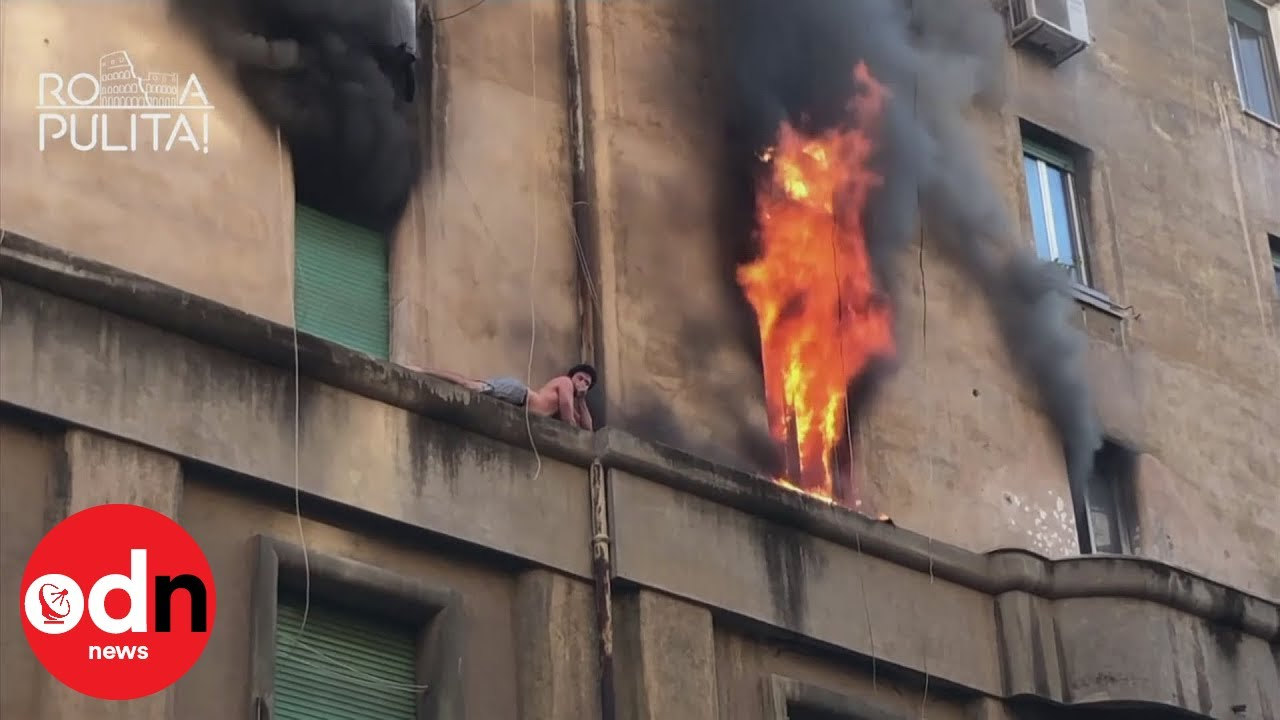 Man clinging to ledge in Rome as Fire blazes around him.