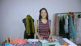 Female fashion designer giving a smile while working in her fashion boutique