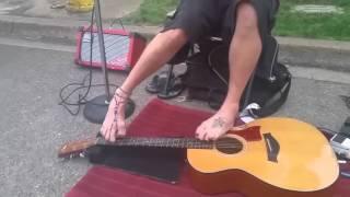 Уличный музыкант без рук играет на гитаре