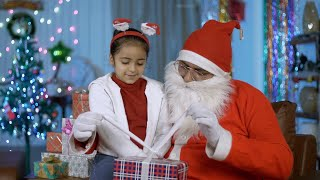 Old Santa in glass spectacles opening a wrapped gift box for a smiling Indian kid - Christmas scene