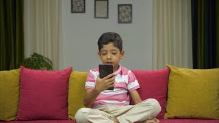 Happy Indian son doing a video call to his dad on his mobile phone