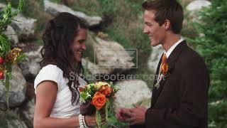Bride Putting Wedding Ring On Groom'S Finger Outdoors