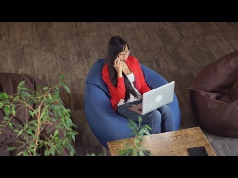 Asian Woman Working In Loft Sitting On Bean Bag Chairs | Stock Footage