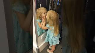 Little girl kissing herself in mirror