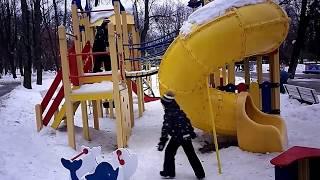 Близнецы на детской площадке с трубой для спуска и горками зимой. Подвесной мост.