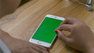 Woman using a smartphone with the green screen on wooden table ( scrolling, tapping the screen)
