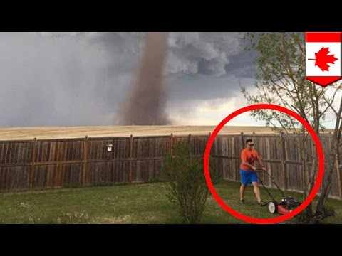 Tornadoes: Picture shows man determined to mow lawn while tornado approaches