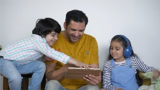 Indian father watching funny videos with his kids on a digital tab - technology concept