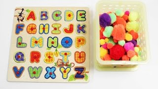 ABC wood puzzle and a bucket full of pompoms