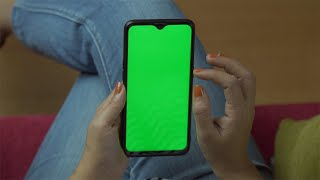 Closeup shot of an Indian female using her smartphone with green mock-up screen