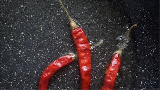 Shot of dried red chilies - laal mirch being dropped in a pan with hot oil