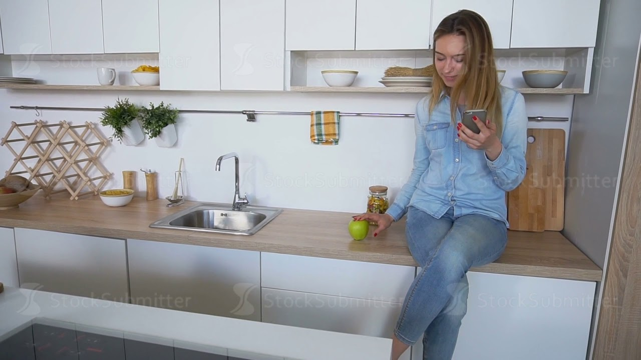 Attractive girl uses smart phone and eats apple, sitting on kitchen ...