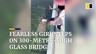 Fearless girl walks across 300-metre-high glass bridge