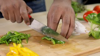 Man chopping green capsicum on a wooden chopping board