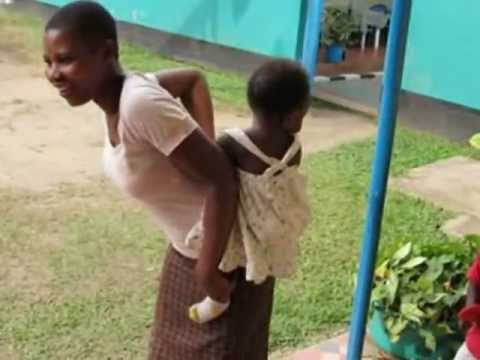 African Lady tying baby on her back.