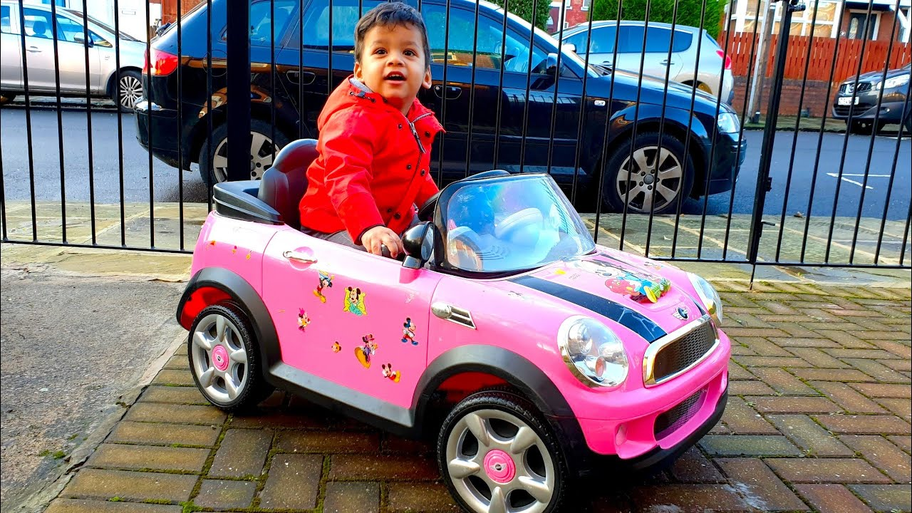Little boy playing pink mini Cooper outside