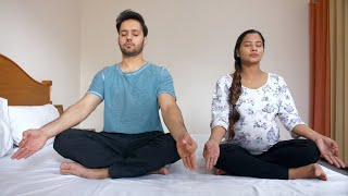A beautiful pregnant woman practicing yoga exercises with her loving husband