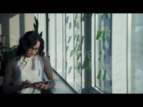 By the Window Stands a Woman with Glasses and Holding a Computer. | Stock Footage - Videohive