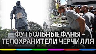 Футбольные болельщики в Лондоне защищают памятники от протестующих