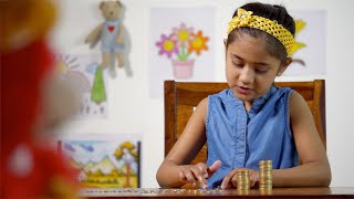 Little girl sitting at the table and counting coins - kids economy, financial saving