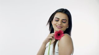 Pretty Indian lady feeling her soft and smooth skin with a pink flower against white background