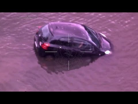 Police rescue a woman from her sinking car after she drove into a river to escape them