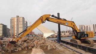 big cat 390f long reach excavator loading a barge with boulders