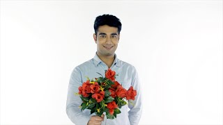 Young attractive male gives a bunch of beautiful flowers - white background