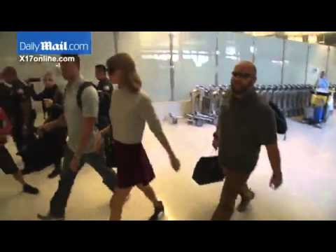 Taylor Swift in a corduroy Mini Skirt and midriff baring knit as she arrives at LAX
