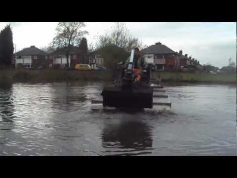 Truxor excavating and dredging silt with clamshell bucket