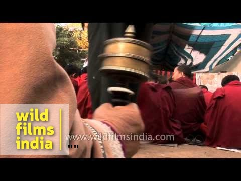 Tibetan worshipper spins a hand-held prayer wheel at Bodhgaya