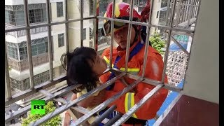 Girl's head stuck by window guard of 7-storey building in China