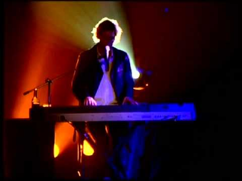 Photo of shaggy-looking man with keyboard, silhouetted in light