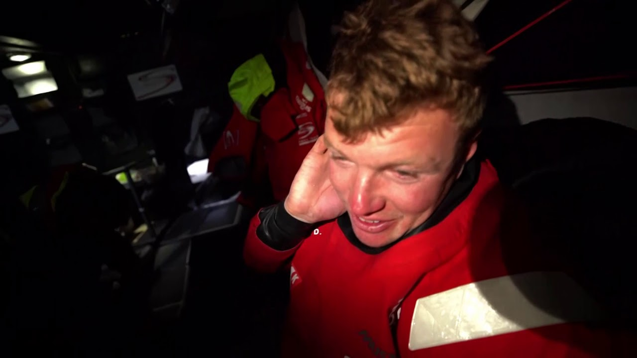 """Stern cam shot with big wind. Double- (or triple- ?) reefed main. Instrument readout at nav station: TWS 38.4. Trystan, below, gets his foulies on. It is pretty windy. Had about 38 knots last night. Upwind, J3, well, pretty well upwind. Gonna be heinous. Cockpit shot. Trystan: Last day now; difficult to gain miles. But as the wind eases we'll be changing sails, so we'll need to do a good job with that. Entering Gothenburg. Keep it going. Spreader cam view of the cockpit. Trystan talks about sleeping as soon as he gets below. """"Love sleep."""" Antonio: Also lots of rain, and it feels like needles when it hits your eyes. Need eye projection. It's what it is; it's the same for everybody. Bow pounding. Antonio: Should arrive today, this evening. He gets confused about what time it is; laughs. """"It doesn't matter. It's daylight all the time."""""""