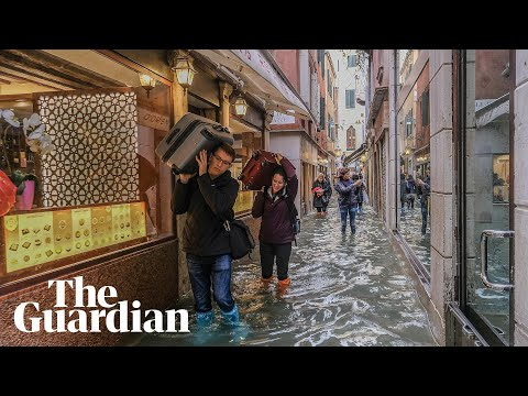 Venice: Tourists and residents wade through flood waters