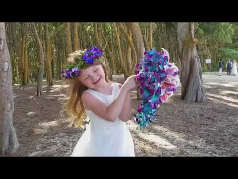 Flower girl plays with her  moms bouquet wedding in Hawaii
