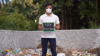 "Indian man showing a slate of ""Stop Pollution"" text with garbage dump in the background"
