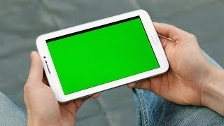 Closeup of hands of a man holding a tablet with green screen