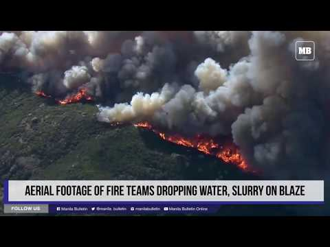 Aerial footage of fire teams dropping water, slurry on blaze